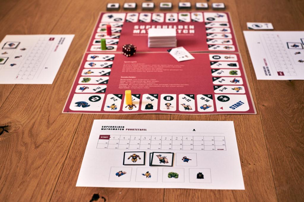 Exemplarische Spielsituation des SMM: Spielbrett mit Figuren, Ereigniskarten und Punktetafel.